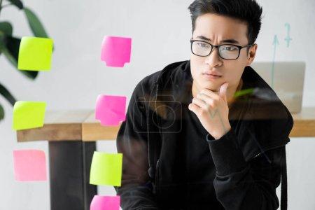 Photo pour Seo asiatiques pensif gérant dans des lunettes regardant le verre avec des notes collantes - image libre de droit