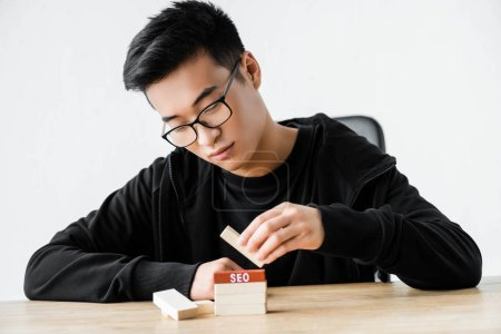 Photo for Asian seo manager playing with wooden rectangles with lettering seo - Royalty Free Image