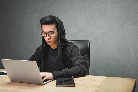 Photo pour Asiatique hacker dans lunettes à l'aide d'ordinateur portable et assis à la table - image libre de droit