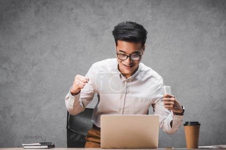 Photo pour Gérant de seo asiatique souriant montrant un geste oui et regardant l'ordinateur portable - image libre de droit