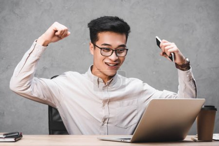 Photo for Smiling asian seo manager showing yes gesture and looking at laptop - Royalty Free Image