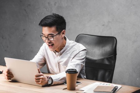 Foto de Smiling asian seo manager sitting at table and holding laptop. - Imagen libre de derechos