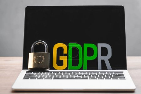 metal padlock and gdpr letters on laptop in office
