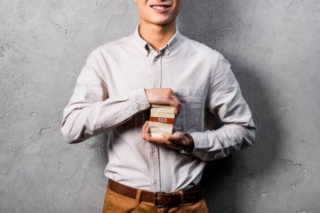 Photo for Cropped view of smiling seo manager holding wooden rectangles with lettering seo - Royalty Free Image
