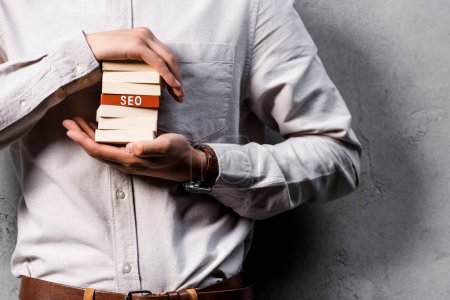 Photo for Cropped view of seo manager holding wooden rectangles with lettering seo - Royalty Free Image