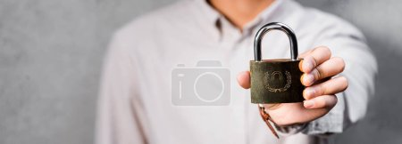 panoramic shot of seo manager holding metal padlock in office