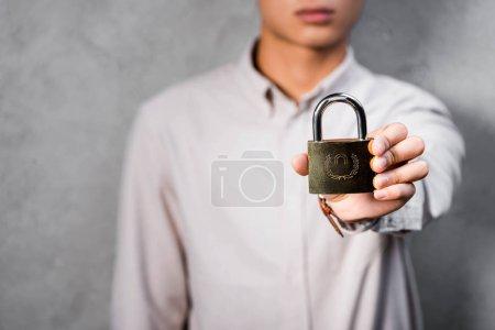 Photo pour Crochet vue de seo manager tenant un cadenas en métal dans son bureau - image libre de droit