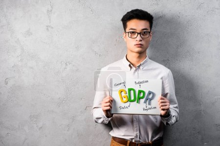 Photo pour ASAAN business man holding paper with gdpr lettering and looking at camera - image libre de droit
