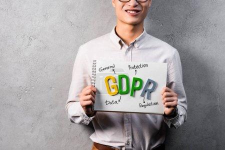Photo pour Vue recadrée d'un homme d'affaires souriant tenant du papier avec lettrage gdpr - image libre de droit