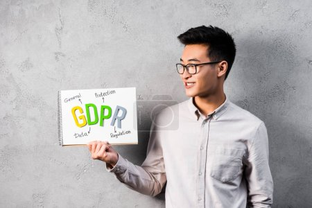 Photo pour Sourire asiatique homme d'affaires tenant et regardant le papier avec gdpr lettrage - image libre de droit