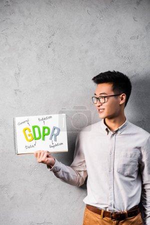 Photo pour Un homme d'affaires asiatique souriant tenant et regardant du papier avec des lettres gdpr - image libre de droit