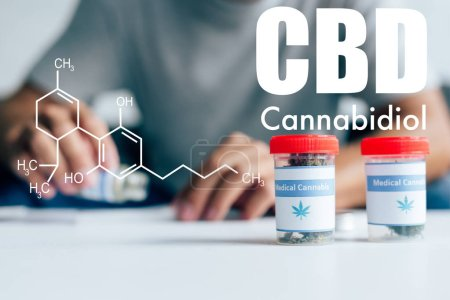 Photo pour Selective focus of bottles with medical cannabis on table with man on background with cbd molecule illustration - image libre de droit