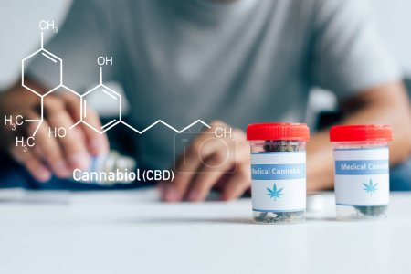 Photo for Selective focus of bottles with medical cannabis on table with man on background with cbd molecule illustration - Royalty Free Image