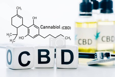 Photo for Selective focus of cubes with cbd lettering near oil and stethoscope isolated on white with cbd molecule illustration - Royalty Free Image