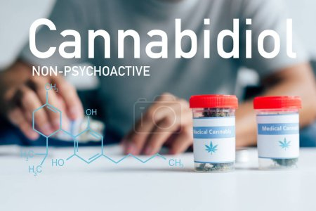 Photo for Selective focus of bottles with medical cannabis on table with man on background with non-psychoactive cbd illustration - Royalty Free Image