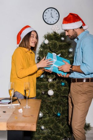 happy bearded man giving present to asian woman in santa hat
