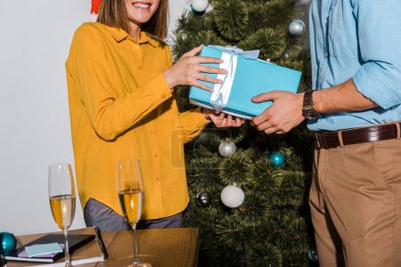 cropped view of man giving present to woman near christmas tree