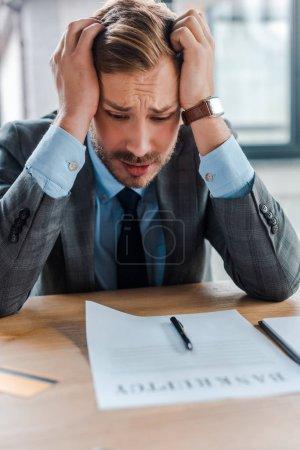 Photo pour Focalisation sélective d'un homme d'affaires frustré regardant du papier avec des lettres de faillite - image libre de droit