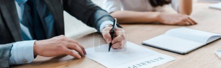 Photo for Panoramic shot of businessman holding pen near document and businesswoman in office - Royalty Free Image