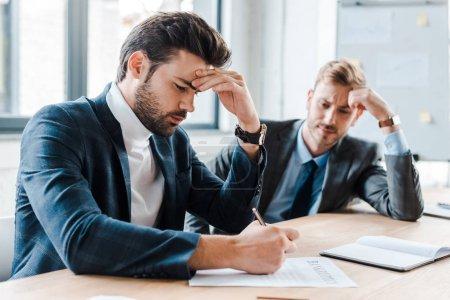 Photo pour Focus sélectif d'un bel homme d'affaires barbu tenant un stylo près d'un document et d'un collègue en fonction - image libre de droit