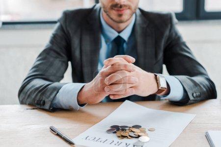 Foto de Vista panorámica del hombre de negocios sentado con las manos cerradas cerca de las monedas y el documento sobre la mesa - Imagen libre de derechos