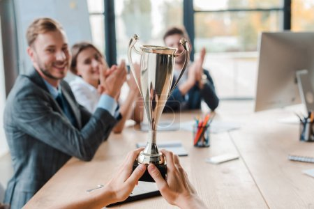 Photo for Cropped view of businesswoman holding champion cup near coworkers in office - Royalty Free Image