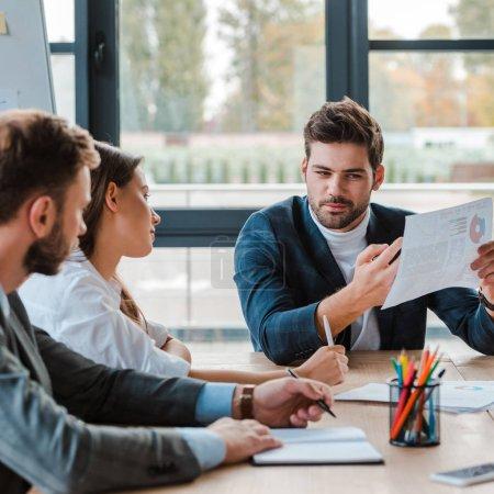Photo pour Foyer sélectif de beaux hommes d'affaires tenant des graphiques et des graphiques tout en étant assis près de collègues dans le bureau - image libre de droit
