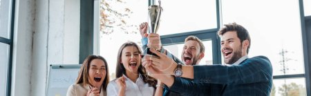 Photo for Panoramic shot of excited multicultural businesswomen and businessmen looking at trophy in office - Royalty Free Image