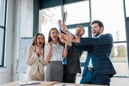 Photo for Happy businessmen and multicultural businesswomen holding trophy in office - Royalty Free Image
