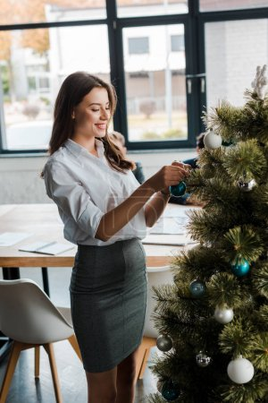 Photo for Cheerful businesswoman standing near decorated christmas tree in office - Royalty Free Image