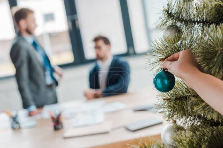 Photo for Cropped view of woman touching christmas ball on christmas tree near businessmen in office - Royalty Free Image