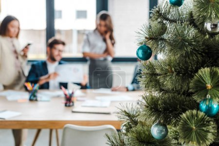 selective focus of decorated christmas tree near multicultural coworkers in office
