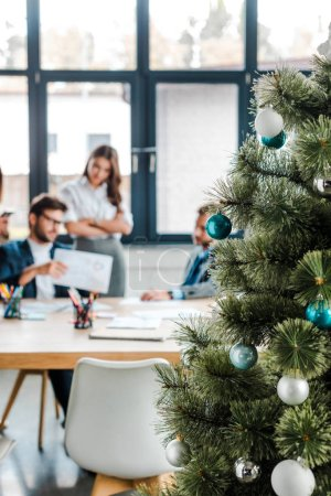 selective focus of decorated christmas tree near coworkers in office