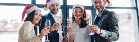 Photo pour Photo panoramique de femmes et d'hommes d'affaires multiculturels heureux dans des santa chapeaux tenant des verres de champagne en fonction - image libre de droit
