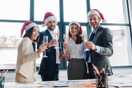 Photo pour Foyer sélectif des femmes d'affaires multiculturelles heureuses et des hommes d'affaires dans les chapeaux de Santa tenant des verres de champagne dans le bureau - image libre de droit