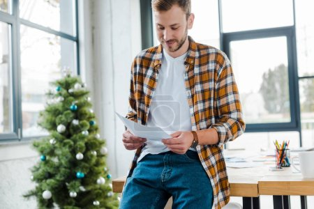 Photo for Selective focus of happy man holding document near decorated christmas tree - Royalty Free Image