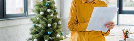 Photo for Panoramic shot of woman holding paper near decorated christmas tree - Royalty Free Image