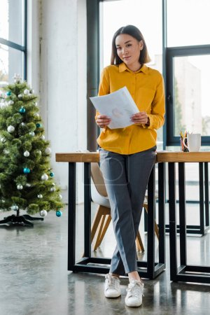 asian businesswoman holding charts and graphs near decorated christmas tree