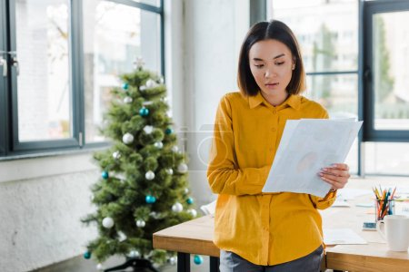 Photo for Attractive asian businesswoman holding charts and graphs near decorated christmas tree - Royalty Free Image