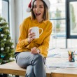 cheerful asian woman in santa hat with with coffee near decorated christmas tree