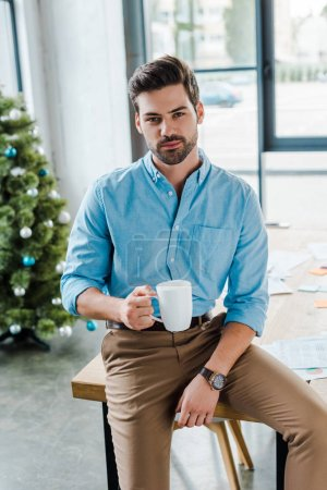 Photo for Selective focus of bearded man holding cup near christmas tree in office - Royalty Free Image