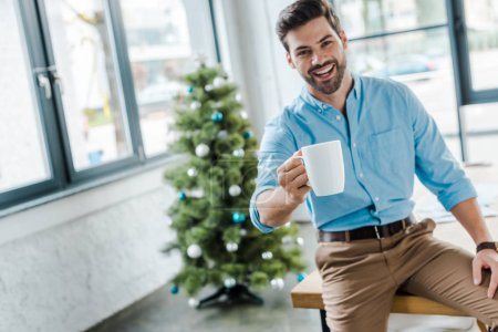 Photo pour Focus sélectif of happy bearded man holding tasse with coffee near christmas tree in office - image libre de droit