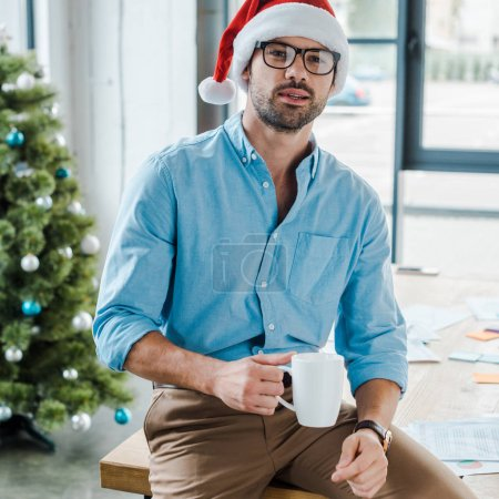 selective focus of happy bearded man in santa hat and glasses holding cup with coffee near christmas tree in office