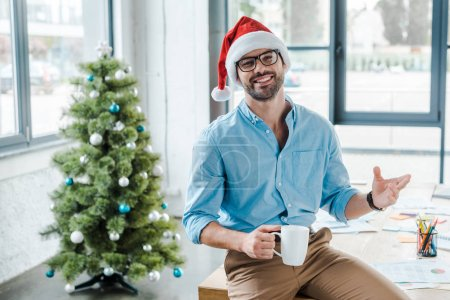 Photo for Selective focus of cheerful bearded man in santa hat and glasses holding cup with coffee near christmas tree in office - Royalty Free Image