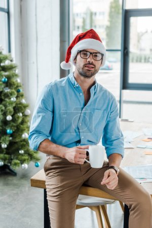 selective focus of bearded man in santa hat and glasses holding cup with coffee near christmas tree in office