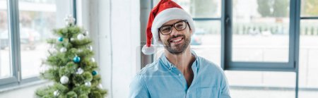 panoramic shot of cheerful bearded man in santa hat and glasses holding cup with coffee near christmas tree in office