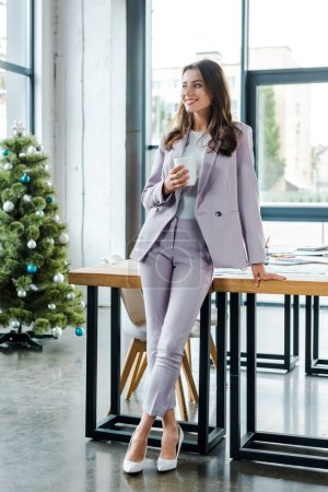 Photo for Cheerful businesswoman holding cup near decorated christmas tree - Royalty Free Image