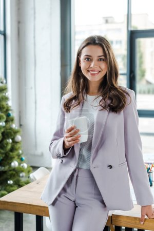 Photo for Happy businesswoman holding cup near decorated christmas tree - Royalty Free Image