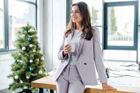 Photo for Happy businesswoman holding cup near christmas tree in office - Royalty Free Image