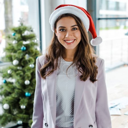 Foto de Happy business woman in santa hat near christmas tree in office - Imagen libre de derechos